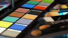 A colorful make-up palette with some brushes lying in front of it Stock Footage