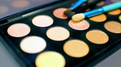 A professional make-up palette with three brushes lying on it,the shot is moving Stock Footage