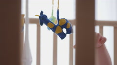 Adorable Curious Baby Reaching For a Toy in His Crib Stock Footage