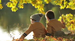 Two children, boys, sitting on the edge of a lake on a sunny autumn afternoon Stock Footage