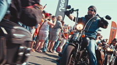 Biker wears short trousers and a red T-shirt at a motorcycle parade Stock Footage