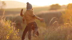 Two adorable children, having fun on sunset, making funny faces and dancing o Stock Footage