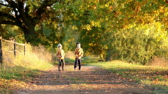 Two children, boys,  walking on the edge of a lake on a sunny autumn afternoo Stock Footage