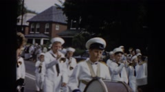 1965: bands troops going procession on roads houses around playing drums Stock Footage