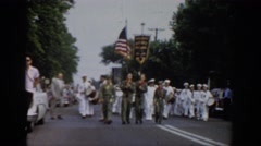 1965: a parade with men in navy uniforms carrying the united states flag through Stock Footage