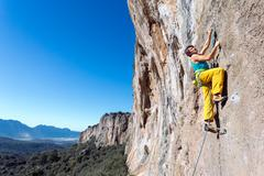 Mature male extreme Climber moving up on rocky Wall Stock Photos