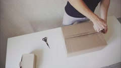 Courier Manstanding in Post Office, Glue Tape Brown Box on All Sides. Stock Footage