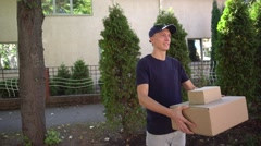 Pedestrian Courier Have Big Bundle in Hand With Smiling on Background of Trees Stock Footage