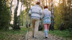 Young couple man and woman wear knitted sweater walking outdoor in autumn forest Stock Footage