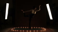 A young woman showing gymnastic exercise in the dark Stock Footage