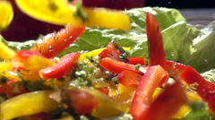 Slow motion chopped vegetables fall on the salad leaves Stock Footage