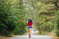 Young male runner marathon running in autumn forest Stock Photos
