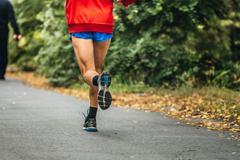 Man feet runner marathon running in autumn Park Stock Photos