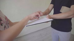 Deliveryman Keeping Small Box in Hand , Giving Pen and Documents to Customer, Stock Footage