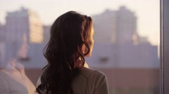 Young beautiful businesswoman admire cityscape at sunset in modern office with Stock Footage