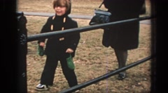 1972: boy in black trying to cross a barricade and his mom helps him PHILADEPHIA Stock Footage