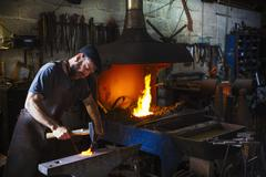 A blacksmith strikes a piece of red hot metal on an anvil Kuvituskuvat
