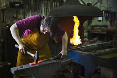 A blacksmith strikes a length of red hot metal with a hammer Stock Photos