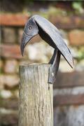 A metal sculpture of a bird nailed to a fencepost Stock Photos