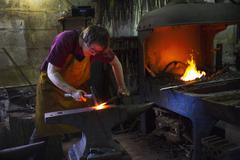A blacksmith striking red hot metal on an anvil inside a workshop Stock Photos