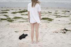 Girl with blond hair in a white t-shirt standing on a sandy beach Stock Photos