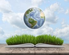 Green landscape covered by grass on an open book with Globe Stock Photos