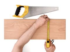 Close up view of a man's hands measuring wooden plank with tape line, isolated Stock Photos