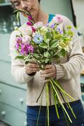 A florist creating a hand tied bunch of fresh flowers Stock Photos