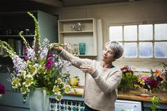 A florist working on a tall vase arrangement of flowers Stock Photos