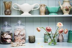 A shelf with vases and ceramic pots and flowers in a vase Stock Photos