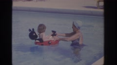 1972: a mother plays in the swimming pool with her toddler floating  Stock Footage