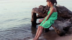 The little girl dropped her nights in Morse water sitting on a log Stock Footage