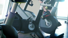 Blue toned footage of a man working out at gym on the exercise bike Stock Footage