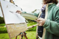 A woman artist working at her easel outdoors applying paint with a hand tool Stock Photos