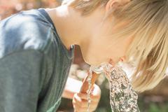 Boy standing in a garden drinking water from a garden hose Stock Photos