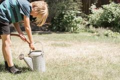 Blond boy standing in a garden filling a watering can from a garden hose Stock Photos