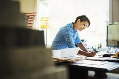 Woman working at a desk in an interior design studio and accessories store Stock Photos