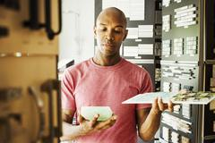 Man looking at merchandise in an interior design store Tile samples Stock Photos