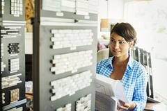 Woman looking at merchandise in an interior design store Tile samples Stock Photos