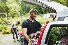 Car parked at a garden centre a man loading flowers into the boot Stock Photos