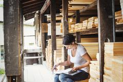 Woman sitting in a lumber yard holding a folder Stock Photos