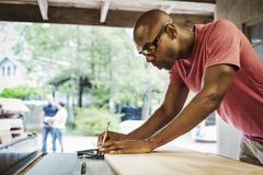Man wearing glasses working in a lumber yard Stock Photos