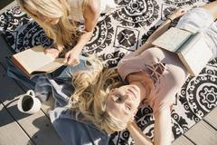 Two blond sisters lying on a jetty reading a book Stock Photos