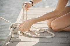 Young woman kneeling on a jetty tying a rope Stock Photos