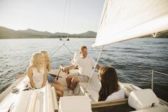Man woman and their two blond daughters on a sail boat Stock Photos