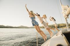 Four people jumping off the side of a sail boat into a lake Stock Photos