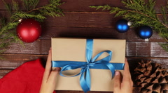 Top view man unwrapping christmas presents at wooden desk hands from above Stock Footage