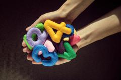 Bunch of multi-colored numbers of felt in the palms Stock Photos