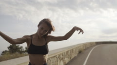 Girl who loves life walking the empty roadway outside the city and enjoying Stock Footage