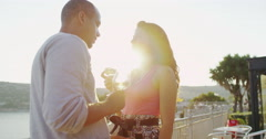4K Romantic couple drinking wine at outdoor bar or restaurant beside the sea Stock Footage
